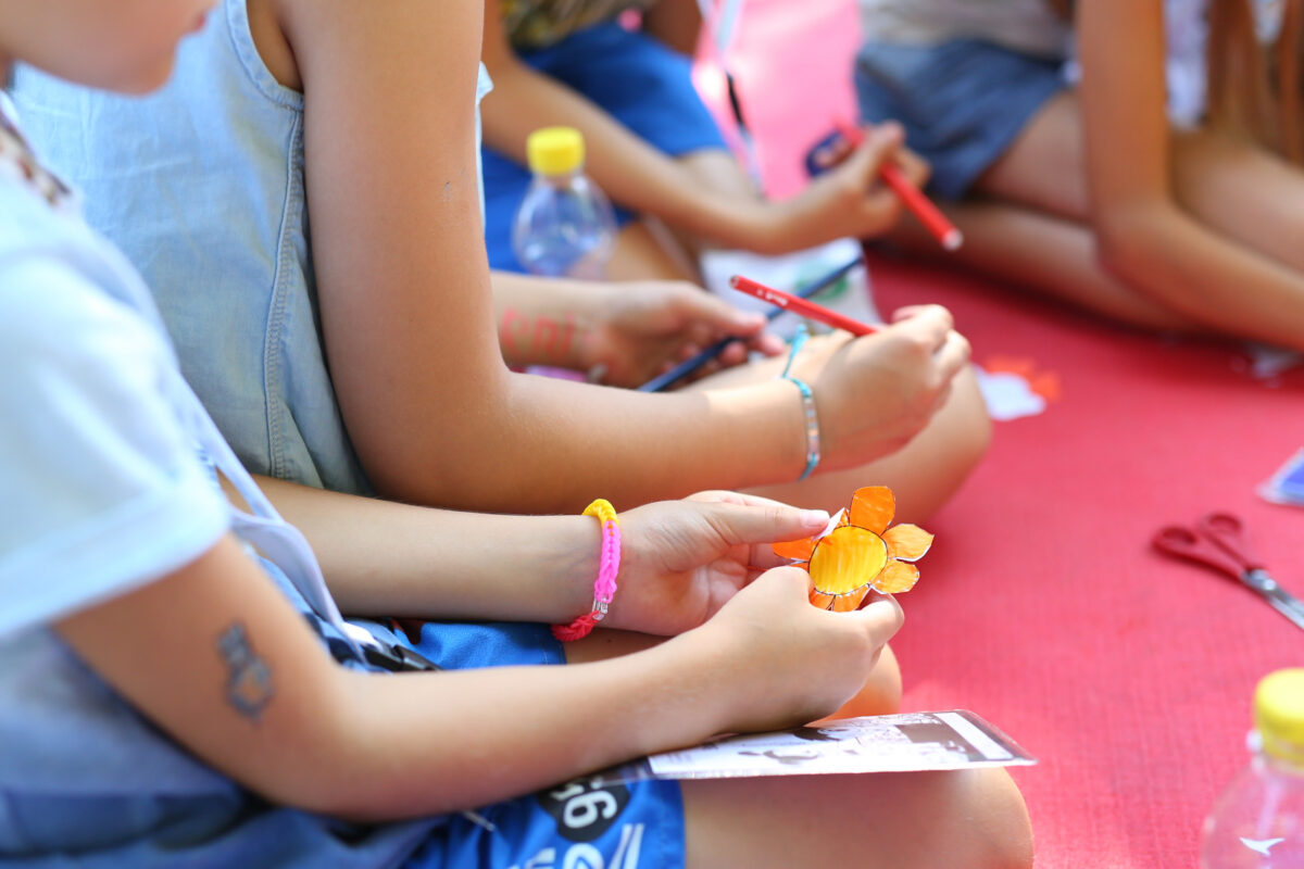 Hände mit Papierblumen und Stiften