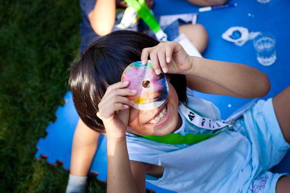 Kind blickt durch Loch in buntem Farbfilter und lacht