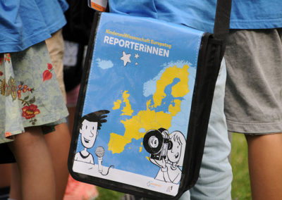 Jemand trägt die KinderuniWissenschaft Europatag ReporterInnen-Tasche
