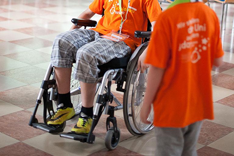 KinderuniWien-Studierender testet das Rollstuhlfahren in einem Workshop